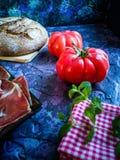 Ветчина, томат, хлеб и травы в составе на темной предпосылке стоковая фотография