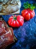 Ветчина, томат, хлеб и травы в составе на темной предпосылке стоковые фото