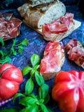 Ветчина, томат, хлеб и травы в составе на темной предпосылке стоковые изображения