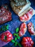 Ветчина, томат, хлеб и травы в составе на темной предпосылке стоковое изображение rf