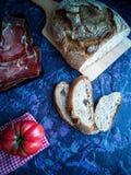 Ветчина, томат, хлеб и травы в составе на темной предпосылке стоковые изображения rf
