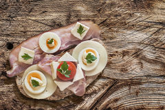 Ветчина яичка сыра бекона и сандвич томата на деревянной предпосылке Стоковое Изображение