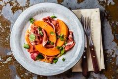 Ветчина serrano Jamon, дыня и салат arugula на серой плите стоковые изображения