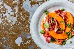 Ветчина serrano Jamon, дыня и салат arugula на серой плите Стоковые Фотографии RF