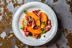 Ветчина serrano Jamon, дыня и салат arugula на серой плите Стоковые Фото
