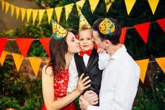 Вечеринка по случаю дня рождения детей Отец и мать семьи держат сына одного года рождения в оружиях и целуют cheekin предпосылка  Стоковые Фотографии RF