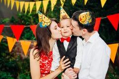 Вечеринка по случаю дня рождения детей Отец и мать семьи держат сына одного года рождения в оружиях и целуют cheekin предпосылка  Стоковые Фото