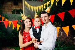 Вечеринка по случаю дня рождения детей темы Отец и мать семьи держа сына одного года на предпосылке растительности и праздничного Стоковые Изображения RF