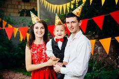 Вечеринка по случаю дня рождения детей темы Отец и мать семьи держа сына одного года на предпосылке растительности и праздничного Стоковое фото RF