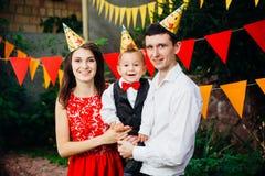 Вечеринка по случаю дня рождения детей темы Отец и мать семьи держа сына одного года на предпосылке растительности и праздничного Стоковое Изображение RF