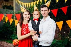 Вечеринка по случаю дня рождения детей темы Отец и мать семьи держа сына одного года на предпосылке растительности и праздничного Стоковые Фотографии RF