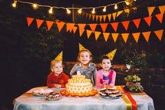 Вечеринка по случаю дня рождения ` s детей 3 жизнерадостных девушки детей на таблице есть торт с их руками и мажа их сторону Поте Стоковая Фотография