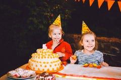 Вечеринка по случаю дня рождения ` s детей 3 жизнерадостных девушки детей на таблице есть торт с их руками и мажа их сторону Поте Стоковые Изображения RF