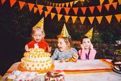 Вечеринка по случаю дня рождения ` s детей 3 жизнерадостных девушки детей на таблице есть торт с их руками и мажа их сторону Поте Стоковое Фото