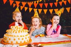 Вечеринка по случаю дня рождения ` s детей 3 жизнерадостных девушки детей на таблице есть торт с их руками и мажа их сторону Поте Стоковые Фотографии RF