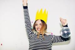 Вечеринка по случаю дня рождения, масленица Нового Года Молодая усмехаясь женщина на белой предпосылке празднуя brightful событие Стоковое фото RF