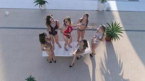 Вечеринка у бассейна, компания радостной женщины в танцы купальника и напиток спирта питья около Poolside на роскошном курорте видеоматериал