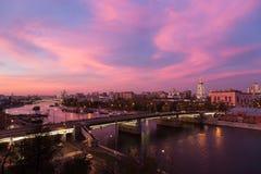 Вечер, взгляд сумерек и ночи, красный заход солнца над рекой Moskva и красными небесами, новый монастырь спасителя и мост Novospa стоковое фото