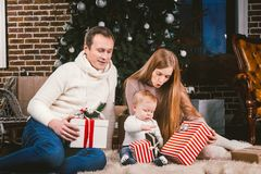 Вечер рождества семьи праздничный Люди семьи 3 кавказские сидя под рождественской елкой хвойного дерева на поле carpe стоковое фото rf