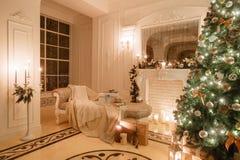 Вечер рождества светом горящей свечи классические квартиры с белым камином, украшенным деревом, яркой софой, большими окнами Стоковое Изображение