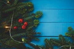 Вечнозеленая ветвь с красными ягодами на голубых досках стоковые изображения