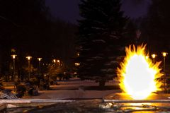 Вечные ожога пламени в сумерках ночи, и в расстоянии одном могут увидеть переулок загоренный уличными фонарями стоковое изображение