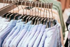 Вешалки с голубыми рубашками человека стоковые изображения