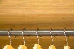 5 вешалок в ряд на сером баре в деревянном шкафе стоковые фотографии rf