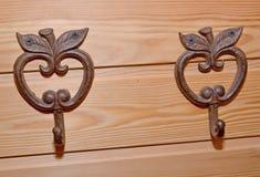 2 вешалки крюков металла в форме яблок на деревянной стене Стоковые Изображения