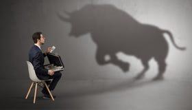 Вещества бизнесмена оставаясь и предлагая к огромной тени быка стоковые фотографии rf