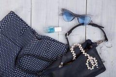 вещество моды - сумка, брюки, солнечные очки, маникюр, ювелирные изделия жемчуга на белой деревянной предпосылке стоковое фото rf