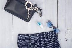 вещество моды - сумка, брюки, солнечные очки, маникюр, ювелирные изделия жемчуга на белой деревянной предпосылке стоковая фотография