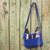 Вещи от открытого портмона дамы Аксессуары ` s косметик и женщин упали из голубой сумки Стоковое Фото