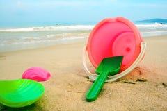 Ведерко ` s детей и покрашенные прессформы на пляже в песке стоковая фотография