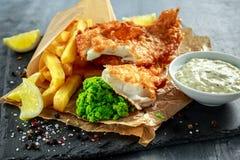 Великобританские традиционные рыбы и обломоки с помятыми горохами, соусом тартара на скомканной бумаге стоковое изображение