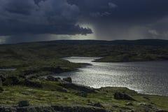 Величественные бурные лучи неба и солнца над озером в горах Стоковые Изображения