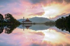 Величественный взгляд мечети Корана Darul во время захода солнца с отражением зеркала в озере Стоковая Фотография