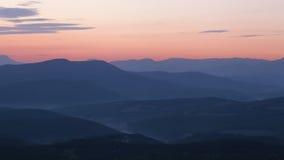 Величественный заход солнца в ландшафте гор. Стоковое Фото