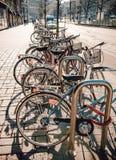 Велосипед автостоянка велосипеда на тротуаре внутри к центру города на восходе солнца Стоковые Изображения