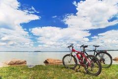 2 велосипеда на живописной предпосылке с небом, водой, травой Стоковые Фото