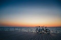 2 велосипеда на пляже на небе восхода солнца, временени Стоковые Фото