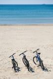 3 велосипеда на пляже на предпосылке моря Стоковые Фото