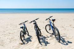 3 велосипеда на пляже на предпосылке моря Стоковая Фотография RF