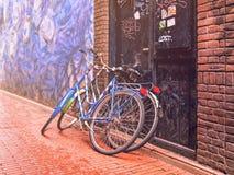2 велосипеда полагаясь против двери на камн-вымощенной проезжей части Стоковое Изображение RF