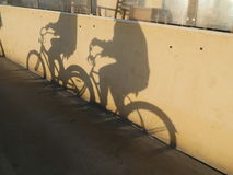 2 велосипеда людей ехать Их тени на стене Стоковая Фотография RF
