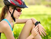 Велосипед задействуя девушка Вахта девушки велосипедиста на умном вахте Стоковая Фотография