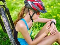 Велосипед задействуя девушка Велосипедист смотрит на умном вахте Стоковые Изображения RF