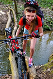 Велосипед задействуя переходить вброд девушки задействуя повсеместно в вода Стоковые Фото