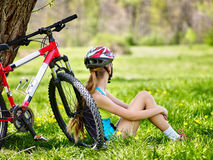 Велосипед задействуя шлем девушки нося Девушка в задействуя сидеть около велосипеда Стоковое Изображение RF