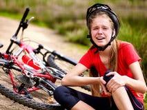 Велосипед задействуя шлем девушки нося Девушка девушки упала с велосипеда Стоковая Фотография RF